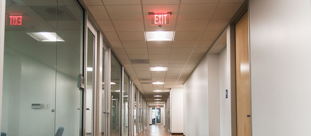 A long hallway in a modern office tower with glass walled offices to the left .