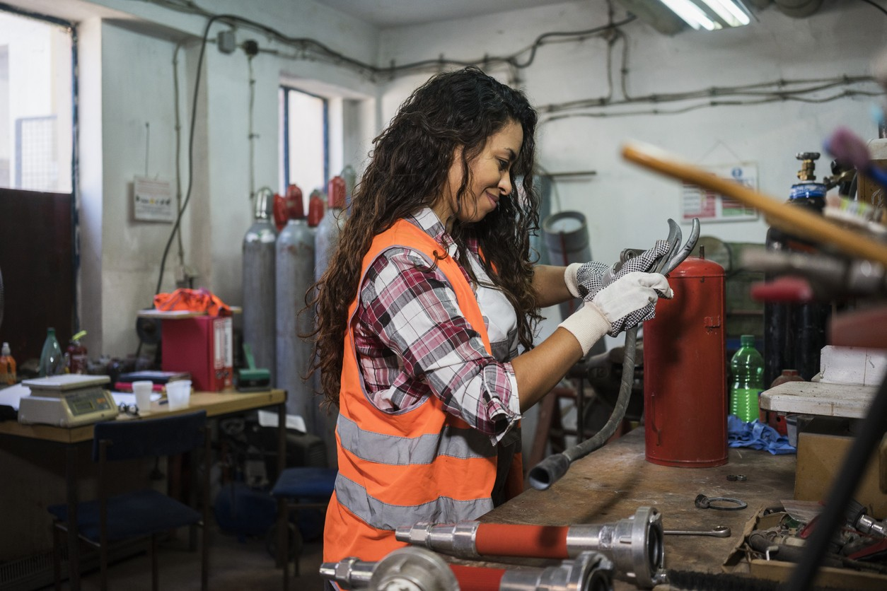 Woman repairing fire extinguisher at workshop